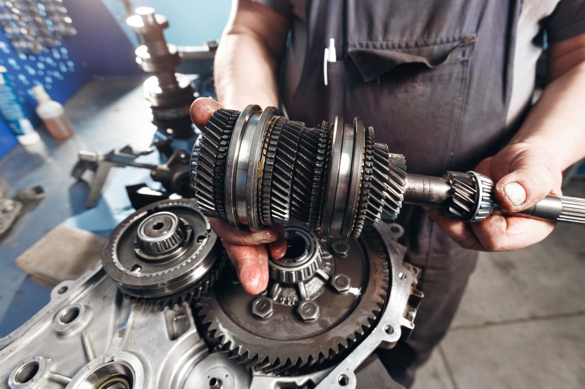 mechanic holding a transmission